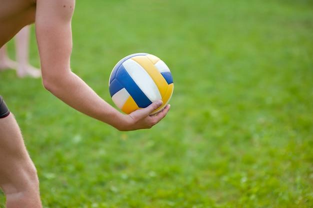 Подросток мальчик играет в пляжный волейбол. волейболист на траве играет с мячом, волейбольный мяч в руке.