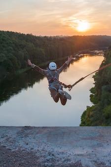 橋から飛び降りる少女。信じられないほどの時間を持つ少女は、バンジージャンプでフリースタイルに取り組んでいます。若い女の子がバンジージャンプで逆のトリックを実行します。日没でジャンプ極端な若い。