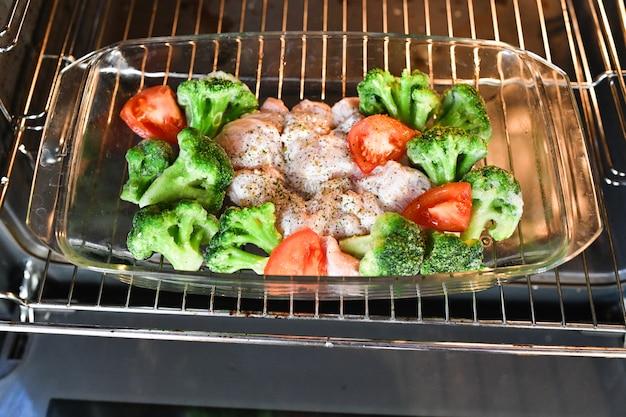 天板に野菜と生の七面鳥。カリフラワースポミドラ。ガラスのベーキングパン、トップビューで生の七面鳥のスパイスを料理します。
