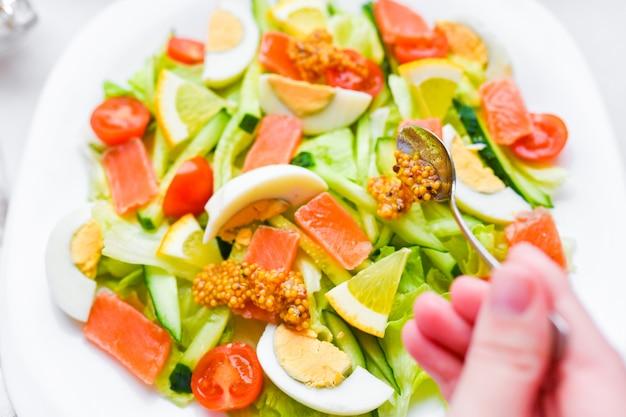 Добавьте горчицу в овощной салат. овощной салат с человеческими руками. на белой тарелке. добавить специи.
