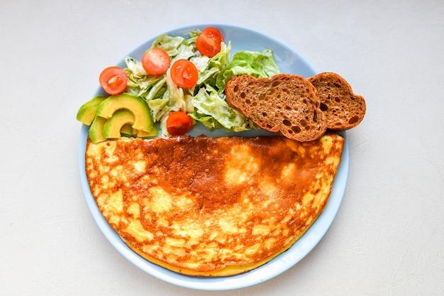 スクランブルエッグと新鮮な野菜。丸皿の上。キノコのオムレツ