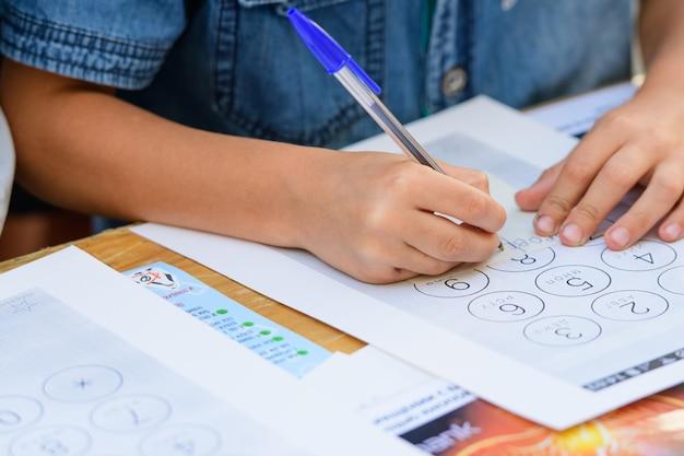 テーブルにいる子供たちは、裁縫をして描きます。美術の授業で子供たちは手作りの紙製品を作ります。