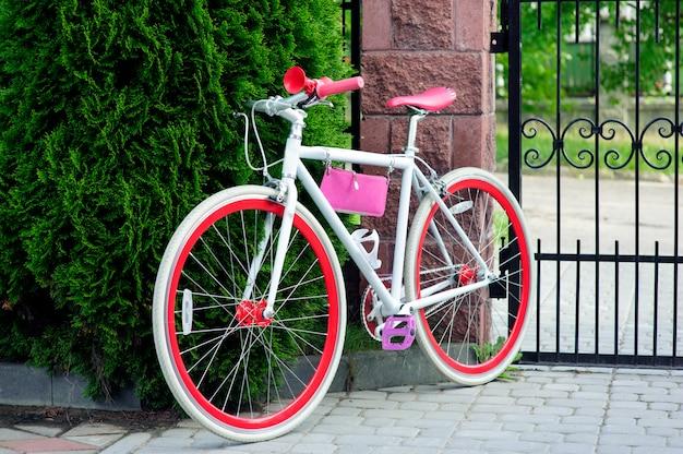 白と赤の自転車。スタイリッシュな女性の赤い自転車。外の晴れた日に立っています。サイクリングに最適な塔。