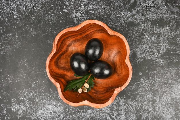 木の板に暗い卵の平面図です。ブラックイースターのコンセプトです。