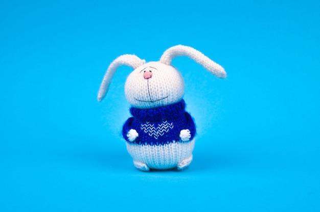 青い背景に、心と青いジャケットの白いニットうさぎ。心を持ったウサギ。執筆のための場所。