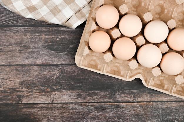 Поднос с яйцами на деревянном столе. вид сверху. эко лоток с яйцами на деревянном столе, минимализм тренд, вид сверху.