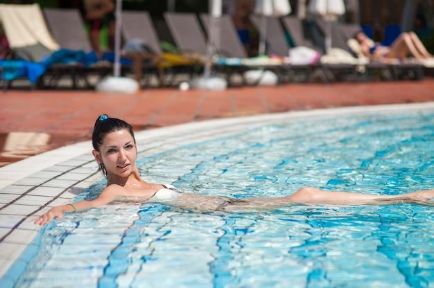 Девушка отдыхает в бассейне. портрет девушки в бассейне. молодая брюнетка купалась у бассейна в отеле. девушка отдыхает и расслабляется. загар в солнечный день.
