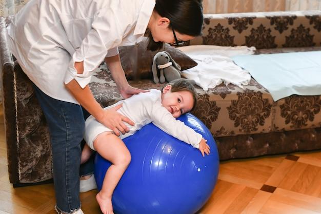 Женщина делает упражнения с ребенком для его развития