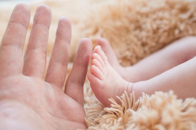手に小さな足。新生児の足を手に持った父。お母さんは入浴後に赤ちゃんの世話をします。親が子供の世話をします。子供の健康と幸せな家族