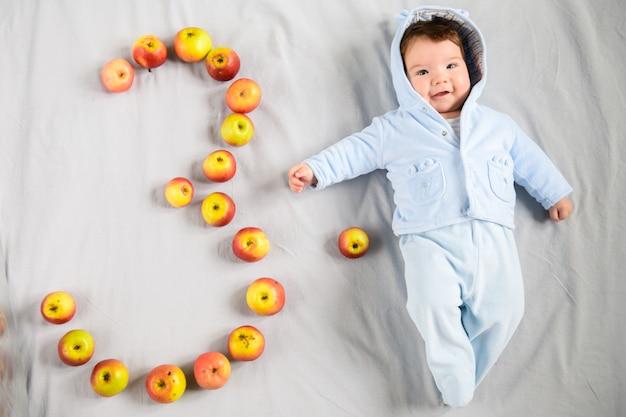 Трехмесячный ребенок. трехмесячный ребенок, на сером фоне. выложил цифру три яблока.