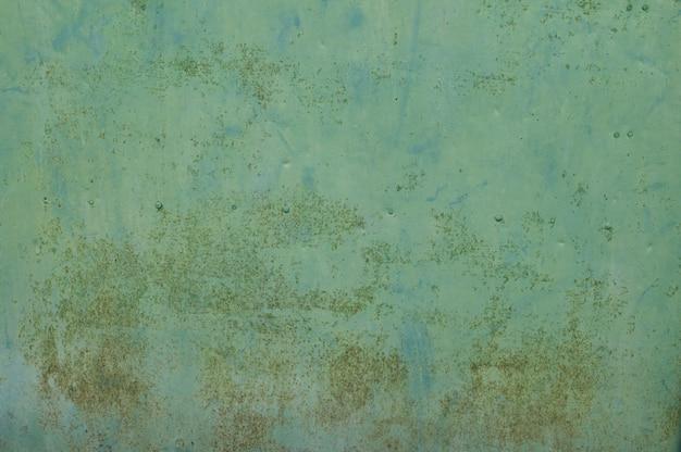 緑の古いオレンジ色の金属製の壁