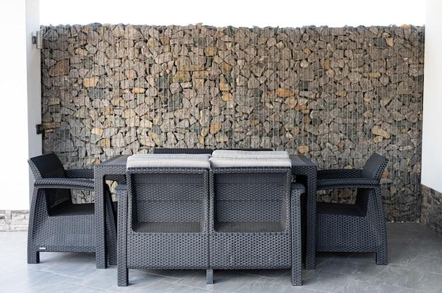 Уличная летняя мебель возле камней