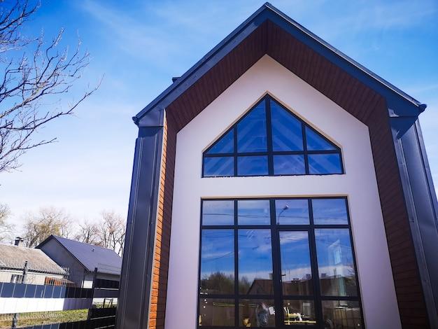 Высокий частный дом с большими окнами