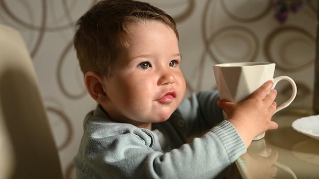 小さな子供は自分でマグカップから水を飲みます。独立した赤ちゃん