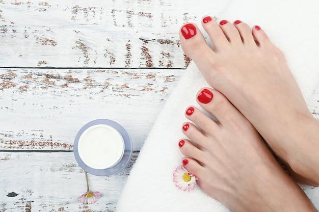 スパと足のケアのコンセプトです。白い巻きタオルで女性の足