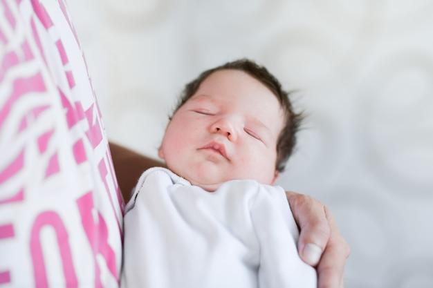 父の腕の中で眠っている赤ちゃん。家で生まれたばかりの赤ちゃんの息子を抱いた若い父親の肖像画。