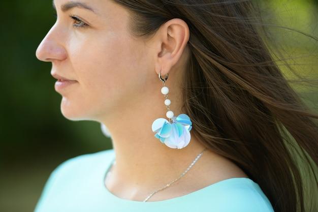 青いイヤリングのブルネット。美しいブルネット。ジュエリーファッション。