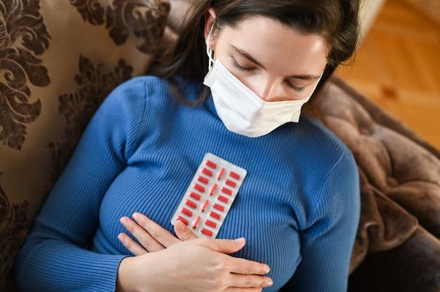 包帯で若い女性は薬を飲む