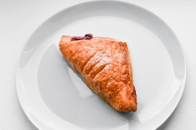 Круассан на белой тарелке. круассан на белой тарелке, вид сверху. пот запеченный десерт в дис.