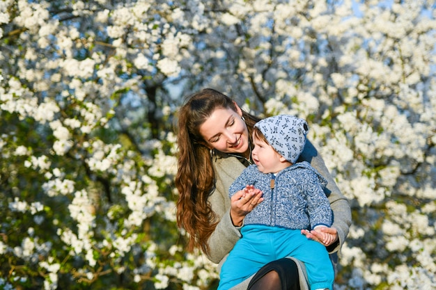 Малыш с мамой радуются в солнечную погоду. очаровательная мама с маленькой дочкой в голубом долго сидела на траве. одетый теплее
