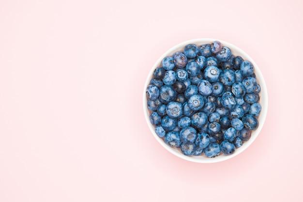 Полезность черники. крупный план ягод голубики с руками в предпосылке светлой тарелки.