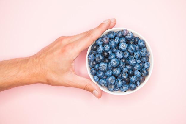 Полезность черники. крупным планом ягоды черники с руками в легкое блюдо