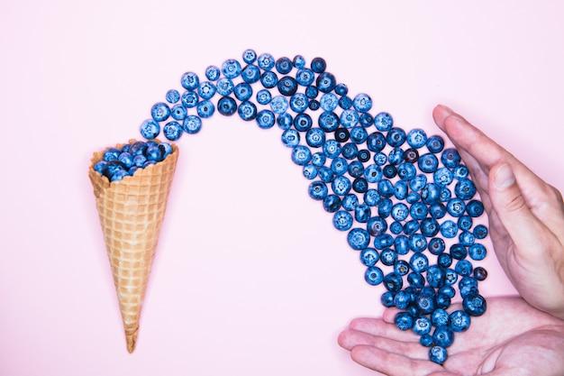 Ягодное мороженое. черника в роге. на фоне для надписи. рука и мороженое. вид сверху концепция витаминов. место для надписи. ягода любовь концепция.
