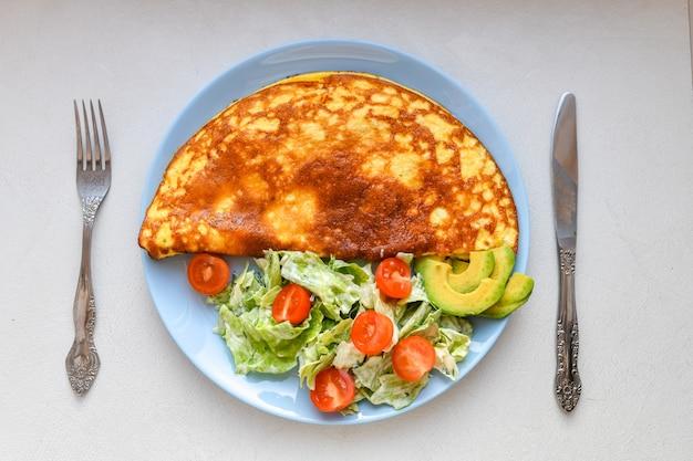 皿に野菜とオムレツ。ブループレート。上からの眺め。朝食に皿に野菜とオムレツ。上からの眺め