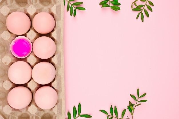 天然卵はピンクです。碑文のための場所。イースターの願い事を書くための白いシート。ミニマルなトレンド、トップビュー。イースターのコンセプトです。