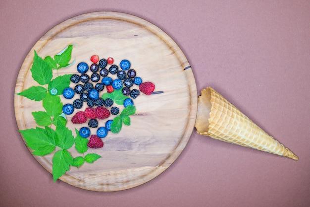 Ягоды и мороженое. композиция из трех видов летних ягод, лежа на текстурированной деревянной тарелке. дикий. ягоды в мороженом.