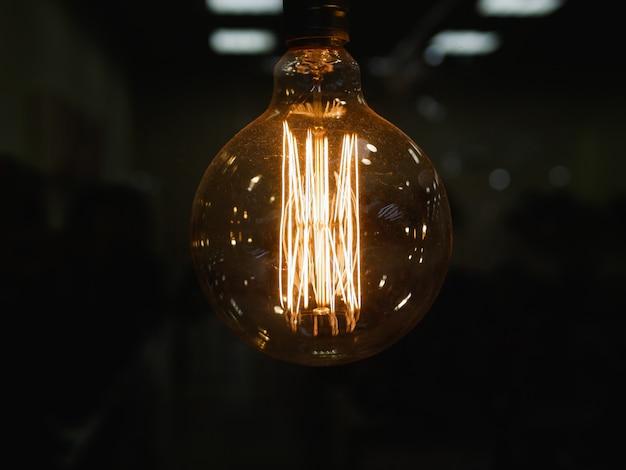 Круглая лампа накаливания. винтажная стилизованная круглая вольфрамовая лампа. накалять в темноте, фото конца-вверх с селективным фокусом. крупный план. темный фон расфокусировать фон.