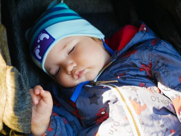散歩用のベビーカーで眠っている赤ちゃん。閉じる。屋外で眠っているかわいい男の子