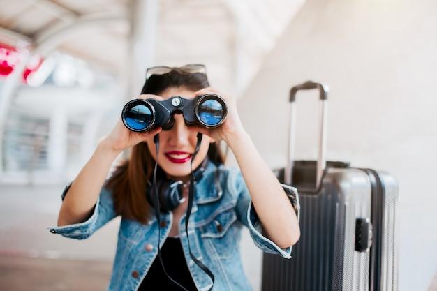 旅行のアジアの女の子は、都市のダウンタウンの旅行のコンセプトの背景と双眼を保持