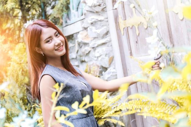 美しいアジアの女の子幸せと緑の庭でポーズをリラックス