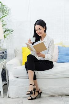 美しいアジアの女性座ってリラックスした読書