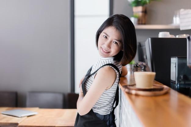 アジアのスマートな女性のカフェオーナーのビジネスのスタートアップの概念