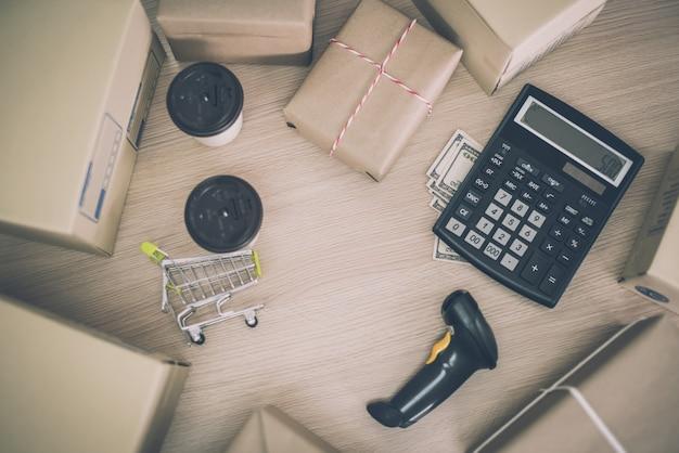 パッケージの計算機と作業机の上の紙の文書とビジネス配信物流アイデアコンセプト