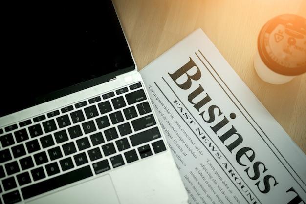 新聞と作業机の上のコーヒーとラップトップのビジネスアイデアコンセプト