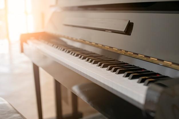 白いカーテンの窓からの太陽の光と黒の光沢のあるピアノ