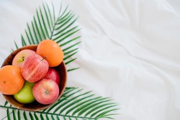 白いベッドの上の木製のボウルに新鮮なフルーツ朝の健康的なライフスタイル