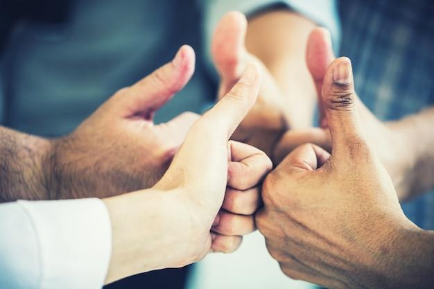 成功した取引とコンセプトのために親指でビジネスチームワークの手洗い業者のグループ