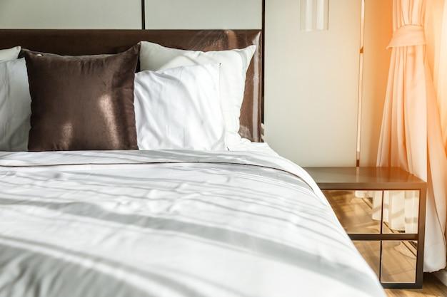 美容室にきれいな白い枕とベッドシーツを備えたベッドメイドアップ。閉じる。日差しの中でレンズの才能。