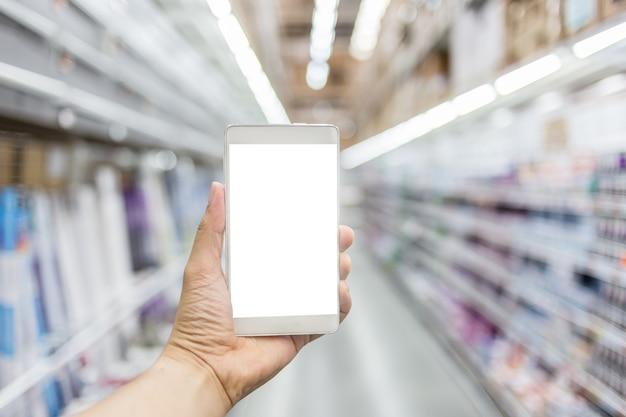 Рука с смартфоном с размытым фоном изображение торгового центра
