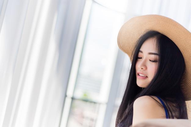 白い部屋の背景とリラックスしたポーズを持つ夏のドレスと帽子とかわいいアジアのグリル
