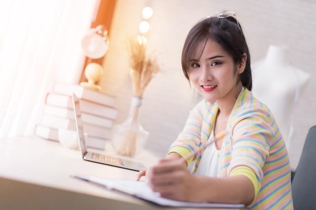 Азиатский красивый модельер, работающий дома с книгой эскиза и ноутбуком