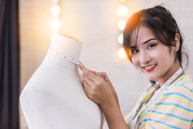 Азиатский красивый модельер, работающий дома с эскизной книжной моделью стенда