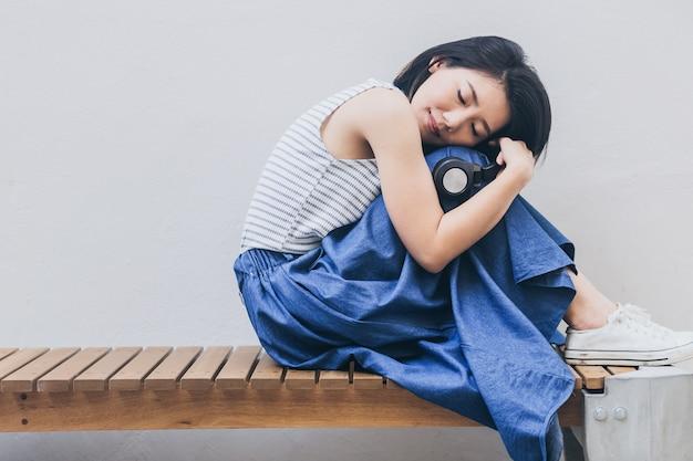 Красивая азиатская женщина в случайном костюме любит музыку из наушников с моментом счастья