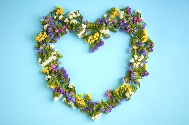 青い表面、ハート形の色の花。フラットレイ