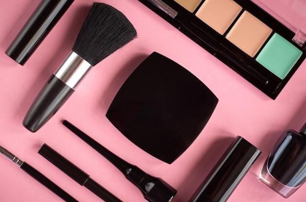 Состав различных косметики на розовом фоне