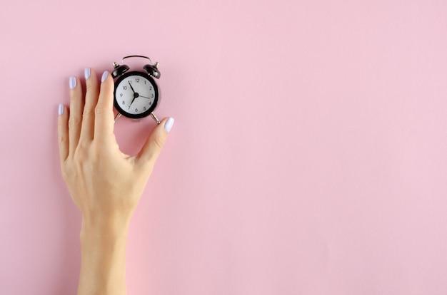 ピンクの背景にアナログ目覚まし時計の組成を持つ手。